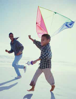 Picture of young boy and mother flying kite.
